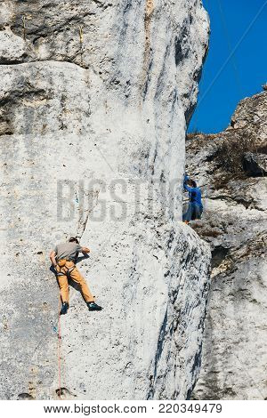 Poland, Podlesice - March 04, 2017: Side view of adult male rock climber on vertical flat wall with poor relief. Gora Zborow is a very popular destination among climbers