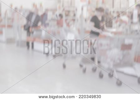 Defocused blurred motion of cashier registers, cashiers, people, customers in supermarket. Cash and credit cards, shopping concept. Light background