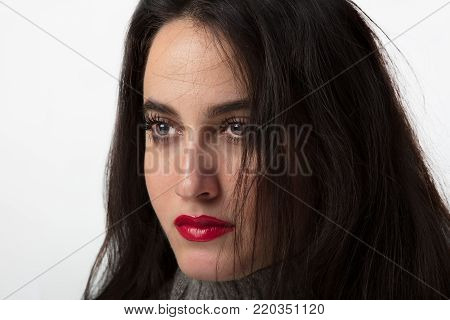 Attractive young woman with long straight brunette hair wearing red lipstick looking off to the side with a serious expression in a cropped beauty portrait over white