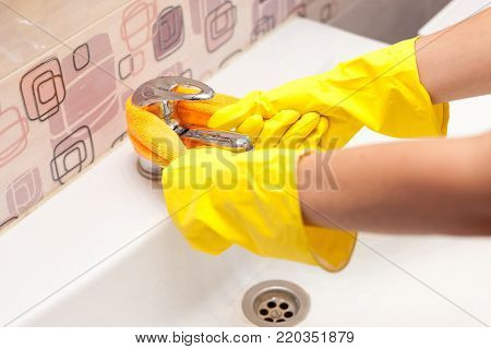 Woman in yellow rubber gloves cleaning toilet seat cover with orange cloth. Bathroom and toilet hygiene