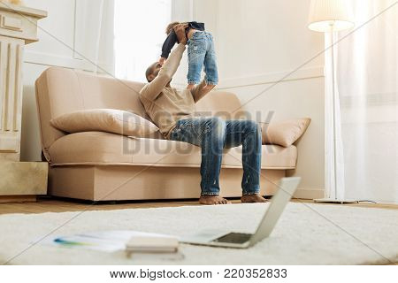 Happy fatherhood. Devoted young afro-american father playing with his son and sitting on the couch and his laptop and papers being on the floor