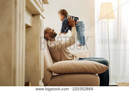 Handsome exuberant afro-american daddy laughing and playing with his child while sitting on the sofa