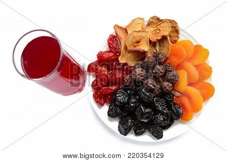 Many different dried fruits (dried apricots, apples, pears, prunes) on a white plate and a glass of compote. Isolated on white background. Multivitamin, antioxidant product.