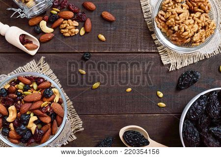 Many different nuts (almonds, cashews, walnuts), dried berries (blueberries, cranberries), prunes, pumpkin seeds in bowls on a dark wooden background. Antioxidant product. Healthy food.
