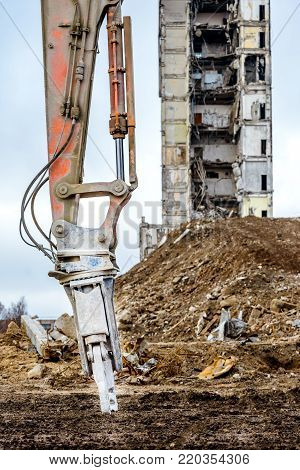 Closeup of hidraulic arm for building demolition demolished highrise industrial building on background