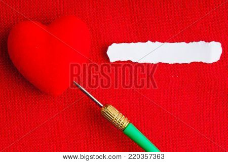 Piece scrap of white paper blank copy space and hearts symbols of love with green dart on red fabric textile material background. Valentines day.