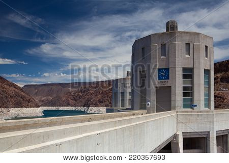Hoover Dam Towers on the blue Lake Mead. Hoover Dam is a concrete arch-gravity dam in the Black Canyon of the Colorado River, on the border between the U.S. states of Nevada and Arizona.