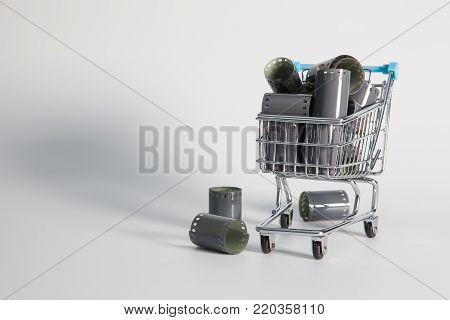 Shopping trolley and tangle of unrolled exposed 35mm film strips over a white background in a retro photography concept