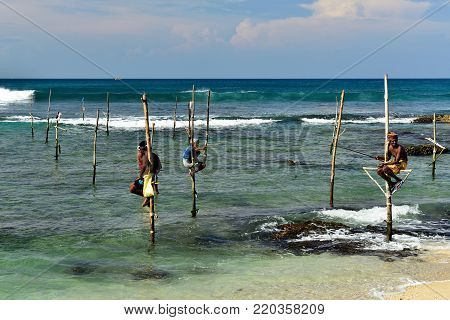 GALLE, SRI LANKA - 02 MARCH 2015: Fishermen on stilts trying to catch a fish on the pole on the coast of Sri Lanka