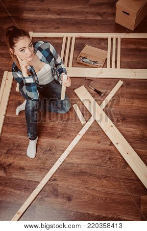 Woman assembling wood furniture. DIY enthusiast. Young girl doing home improvement.