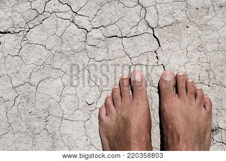 high angle view of the bare feet of a young caucasian man on a cracked dry soil