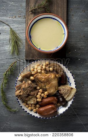 cocido madrileno, typical of Madrid, Spain, with the soup served in an earthenware bowl and the meat and vegetables used in the broth served in a tray, all placed on a rustic wooden table