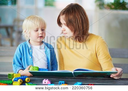 Little Boy Playing With Construction Blocks While His Mother Working On Computer