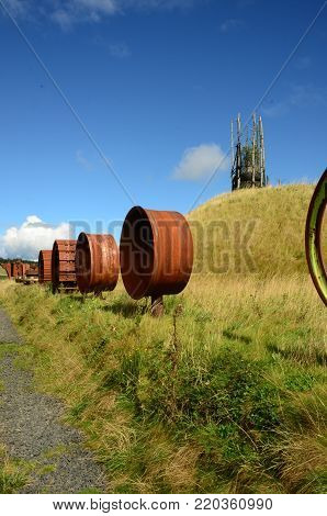 A gravel path along an an avenue of machinery parts at a former opencast mining site near Kelty