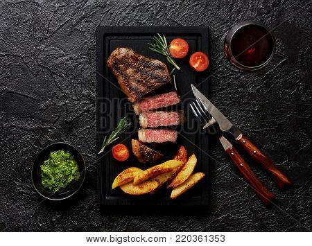 Meat Picanha steak, traditional Brazilian cut with potato wedges, chimichurri sauce and rosemary on black meat cutting board. Steak and a glass of red wine with fork and knife.
