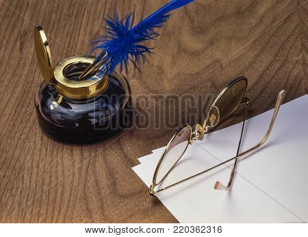 Tools of a writer: inkwell, pen, glasses and paper on a wooden table