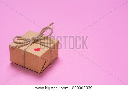 A gift wrapped in kraft paper on a pink background. Paper red heart on a gift box