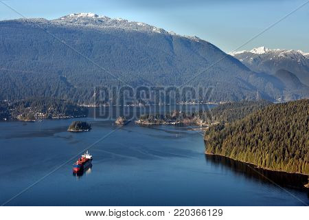 Vancouver Harbor, Ocean Ship in  Burrard Inlet, Indian Arm and Deep Cove on the background scenery of snow-capped mountains and cloudy sky
