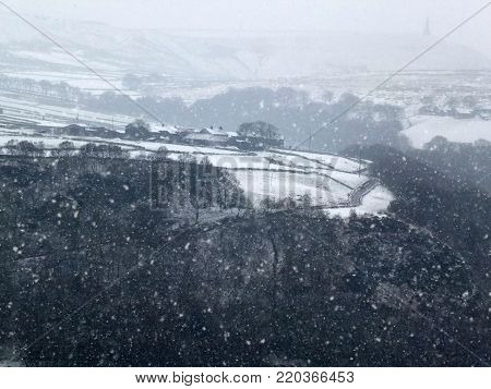 snow falling in a yorkshire dales landscape with winter trees and farms visible on the hills