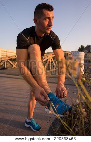 man tying running shoes laces getting ready to run on city at sunny morning