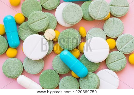 Opioid Pills. Opioid epidemic and drug abuse concept. Different tablets, pills, capsule on a pink background. Heap mix therapy drugs