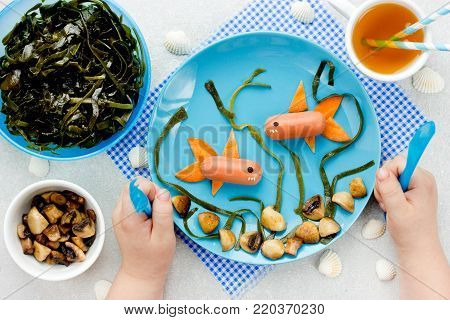 Child hands holding cutlery and eats funny lunch, food art concept, picture on a plate