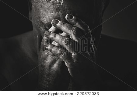 Dramatic close up black and white portrait of depressed old man with hands on face