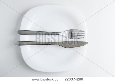 The fork and knife lie on a white plate on a light background. Table Etiquette