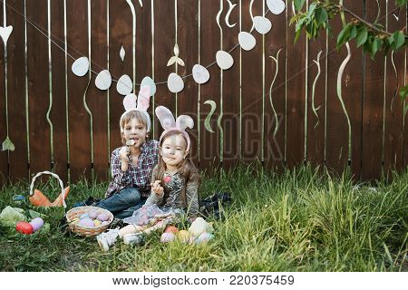 Little girl and boy eat a gingerbread cookie in the shape of the Easter egg. Easter celebration. Laughing children at Easter egg hunt