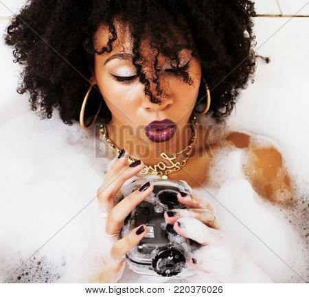 young afro-american teen girl laying in bath with foam, wearing swag jewelry flawless, making selfie, modern lifestyle concept, spa woman