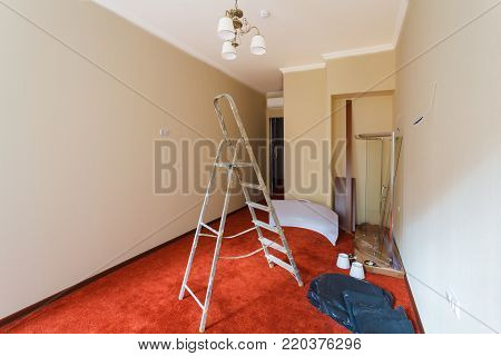 Unfinished interior of upgrade room with ladder  and parts of shower cubicle during on the remodeling, renovating, extension, restoration, reconstruction and construction. (chandelier installation)