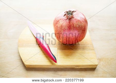 Red pomegranate and red knife.  How to Deseed a Pomegranate. Health benefits of Punica granatum. White bowl with pomegranate seeds. Pomegranate, pomegranate seeds, apple, wild grapes