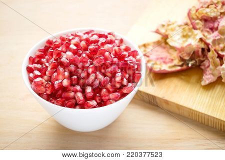 Cleaned pomegranate.  How to Deseed a Pomegranate. Health benefits of Punica granatum. White bowl with pomegranate seeds. Pomegranate, pomegranate seeds, apple, wild grapes