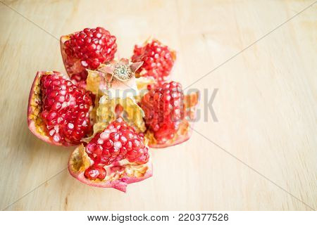 Cleaned pomegranate.  How to Deseed a Pomegranate. Health benefits of Punica granatum. Juicy and raw fruits on a wooden background. Pomegranate, pomegranate seeds, apple, wild grapes