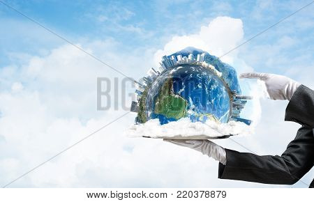 Cropped image of waitress's hand in white glove presenting Earth globe on metal tray and pointing on it with cloudy skyscape on background. 3D rendering. Elements of this image are furnished by NASA. poster