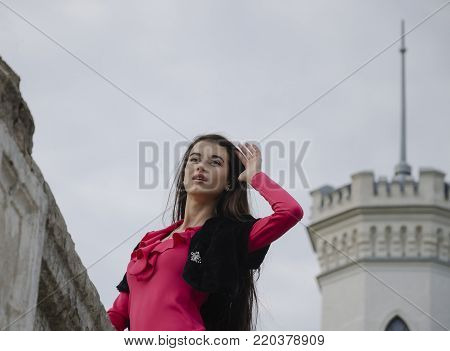 young beautiful girl with long dark hair pensively looking into the distance