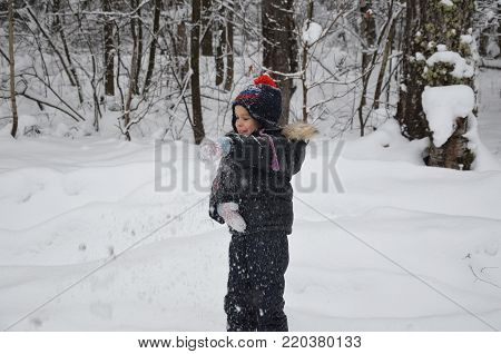 A simpotic little boy throws snow in the winter snow-covered forest, trees in the snow. enjoys the winter. plays snowballs. happy, smiling, laughing with falling snow