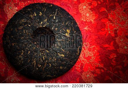 Chinese old black tea puer fire red paper background