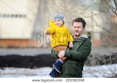Middle age father with his little son together outdoors. Fatherhood concept
