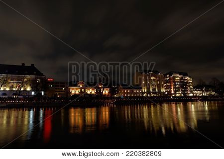NORRKOPING, SWEDEN - DEC 31, 2017: Nightscape of the beautiful river Motala Strom and buildings reflecting in the water in central Norrkoping in Sweden, December 31, 2017