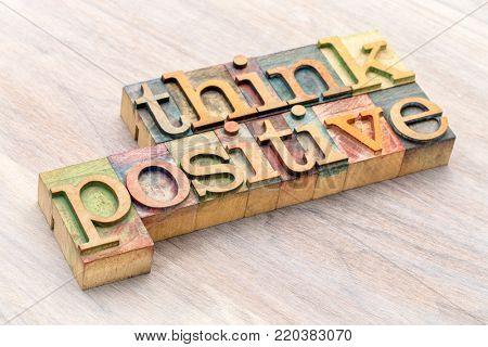 Think positive - word abstract in vintage letterpress wood type blocks against grained wooden background