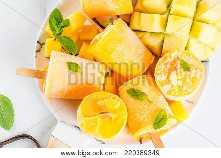 Ice cream, popsicles. Organic dietary foods, desserts. Frozen mango smoothie, with mint leaves and fresh mango fruit, on plate, on white marble table. Copy space