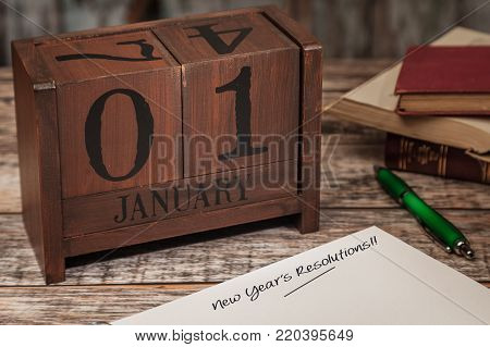 Perpetual Calendar in desk scene with diary page, January 1st, New Years Resolution