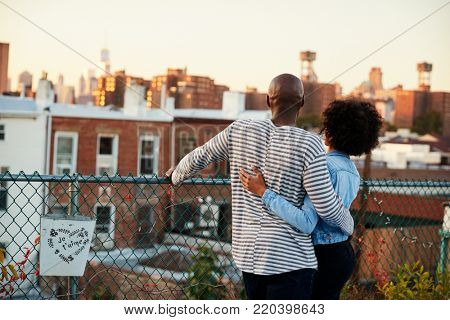 Young black couple embracing on Brooklyn rooftop, back view