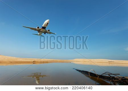 Commercial airplane landing above sea and clear blue sky over beautiful scenery nature background,concept business travel and transportation background
