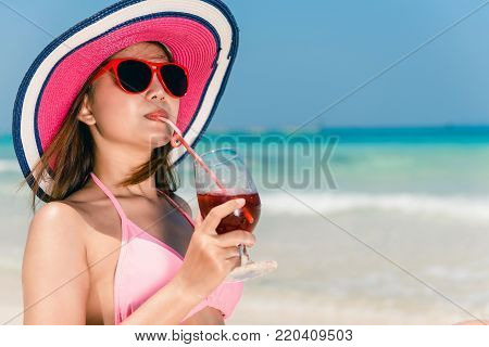 Lifestyle happy young adult asian woman in pink bikini with cocktail in hand and straw hat on beach. Lifestyle outdoors woman portrait. Lifestyle woman summer concept.