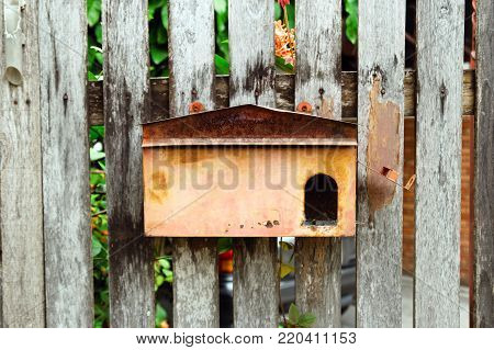 Old shabby postbox on a wooden wall. Chiang Mai, Thailand.