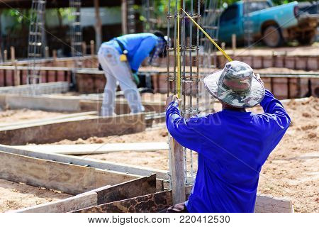 The worker holding measuring tape on formwork at construction site