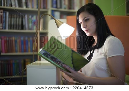 Belarus, the city of Gomel, on November 15, 2017. The grand library. Young woman in library with book in hands