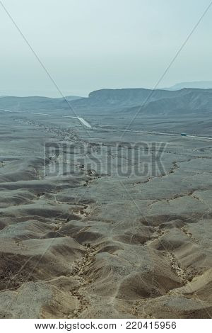 View on desert sunny land and sky near dead sea in Israel. Valley of sand, mountains and stones in hot middle east tourism place. Scenic outdoor infinity on wild land. Summer heat and nobody on photo